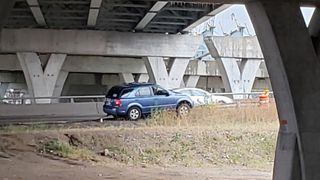 Car gets stuck on I-74 on-ramp retaining wall